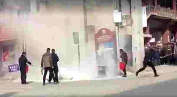 一名警察在自焚現場手持棍棒驅趕圍觀的民眾  照片/載自網絡